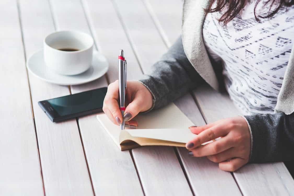 אישה כותבת במחברת על שולחן מעץ שיש עליו קפה וסמארטפון