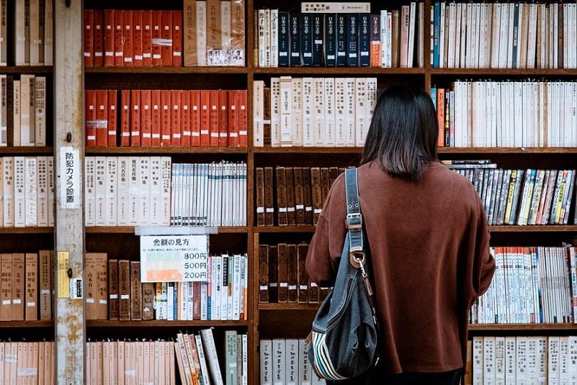 אישה מחפשת ספר בספריה על סיבות לנסיגה בקו השיער