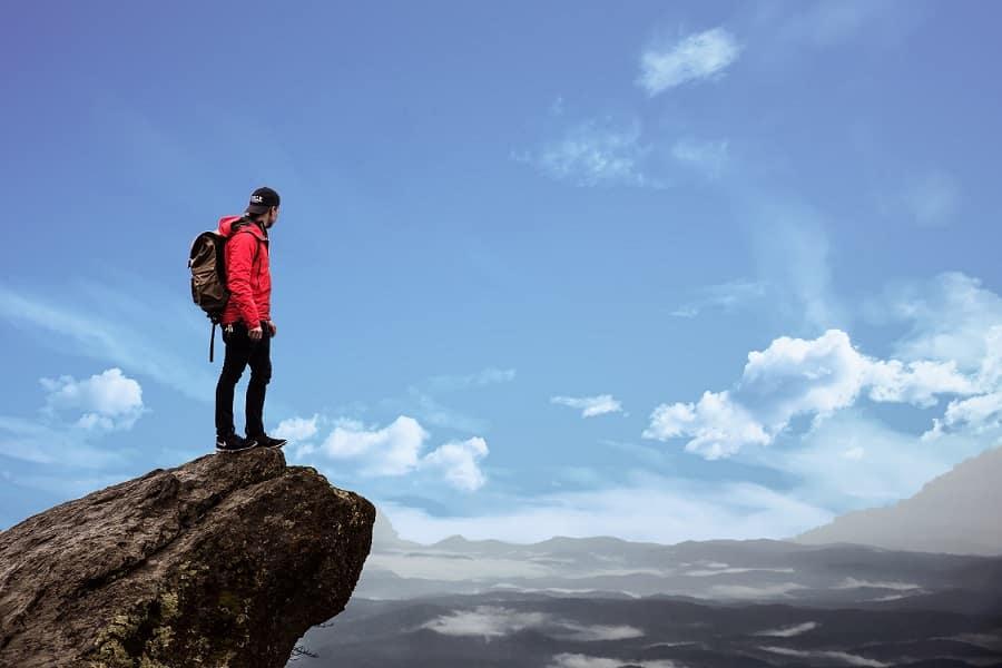 בחור צעיר עומד על קצה של צוק ומסתכל אל עבר האופק