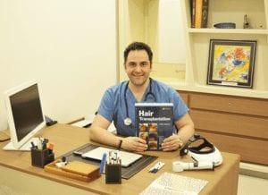 דוקטור לבנט אקאר יושב במשרד שלו ומחזיק ספר על השתלות שיער