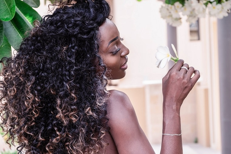 אישה עם שיער שחור ומאוד מתולתל מריחה פרח לבן