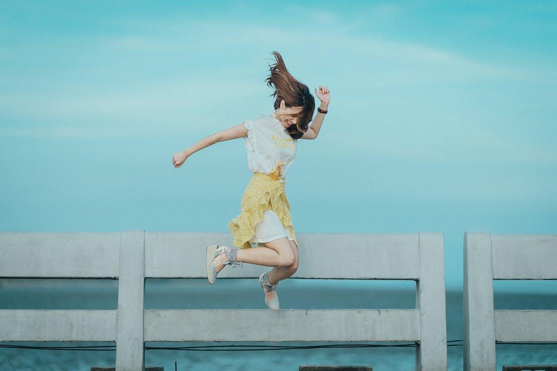 בחורה צעירה קופצת באוויר ומחייכת