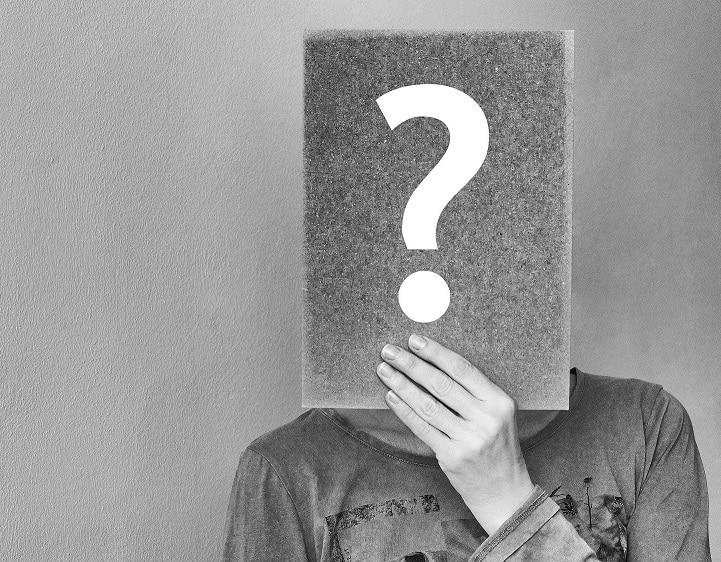 בן אדם מסתיר את הפנים עם פלקט שמצוייר עליו סימן שאלה
