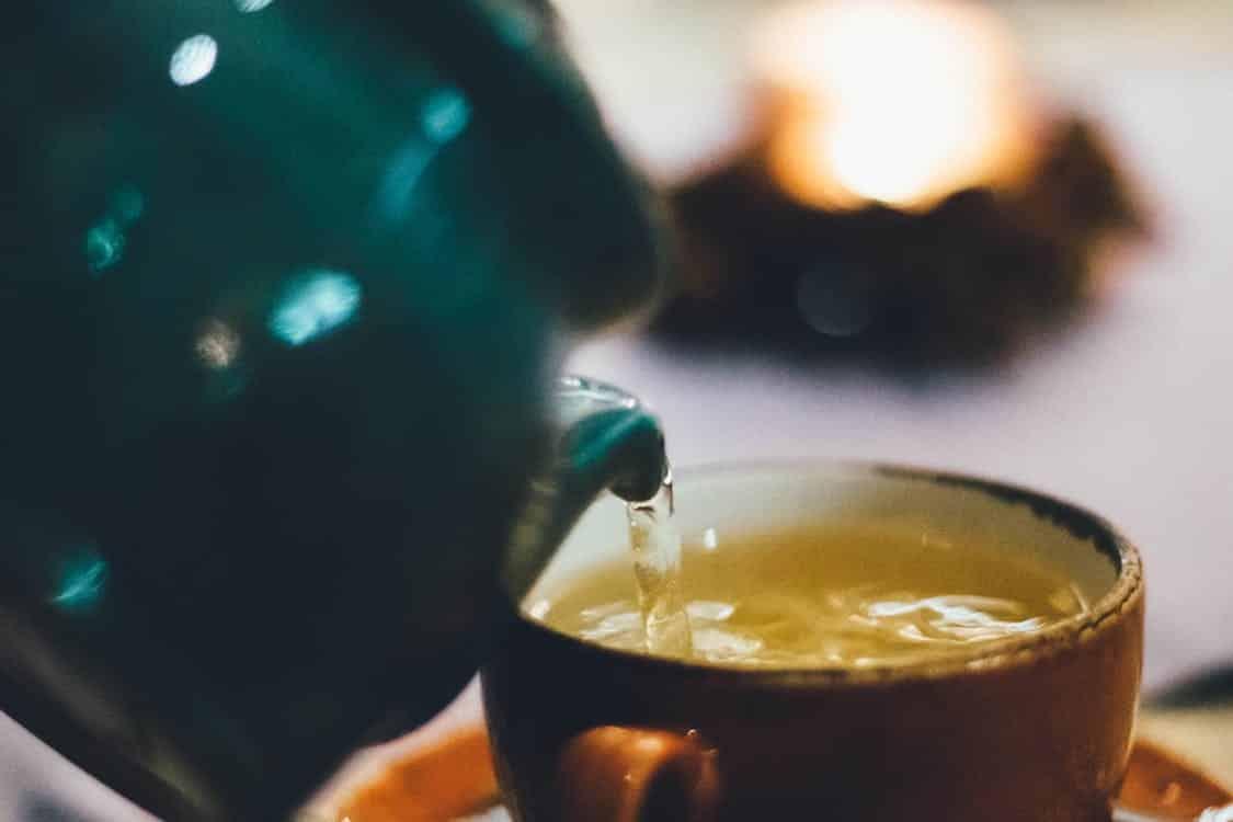 קומקום מוזג תה ירוק לתוך כוס