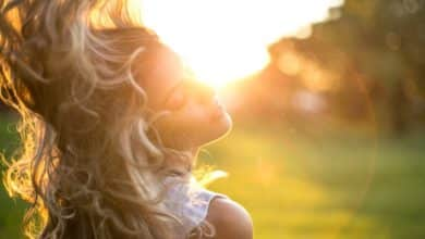 אישה בלונדינית מנופפת בשיער שלה אל מול השמש