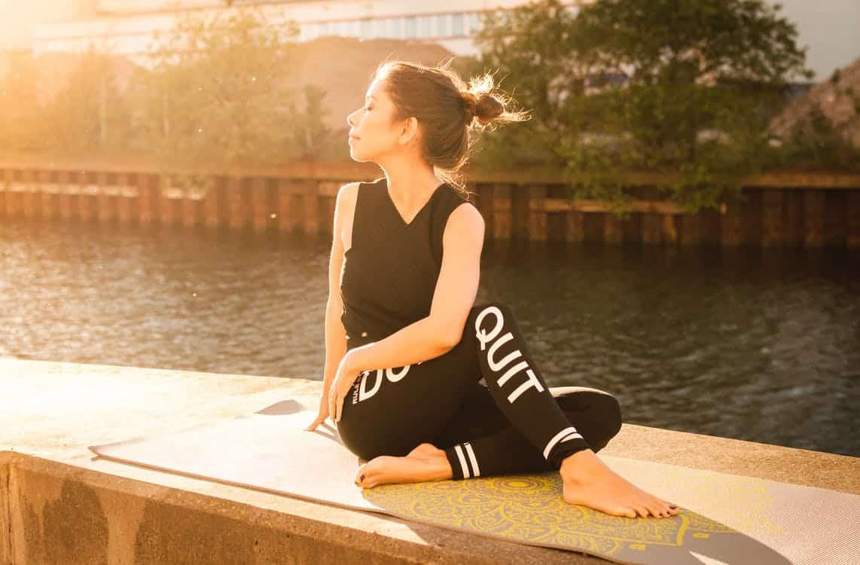אישה צעירה עושה יוגה ליד הנהר בחוץ