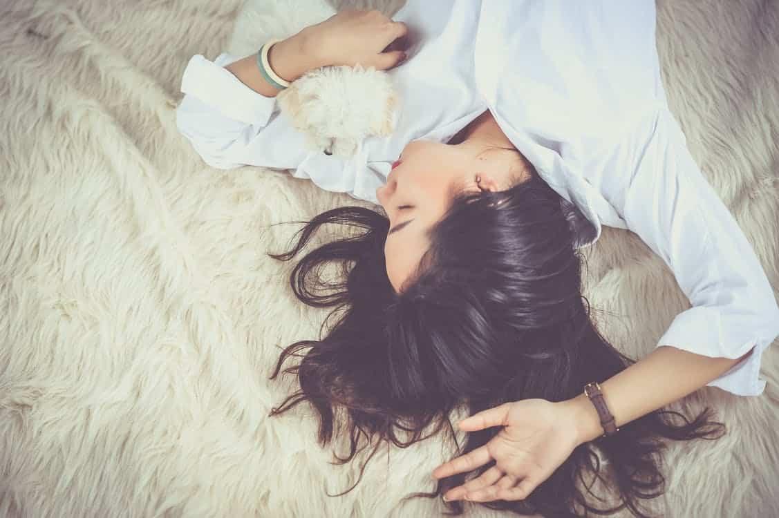 אישה שוכבת על המיטה עם שיער פזור ועיניים עצומות