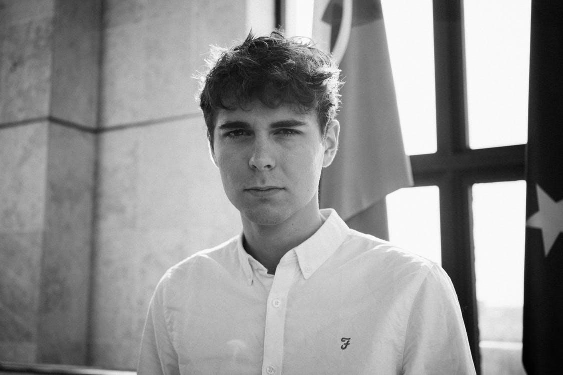 גבר צעיר עם שיער מפוזר מביט למסך בשחור לבן