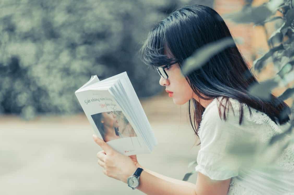 בחורה אסייתית עם משקפיים יושבת וקוראת את הסיפור מאחורי RU58841