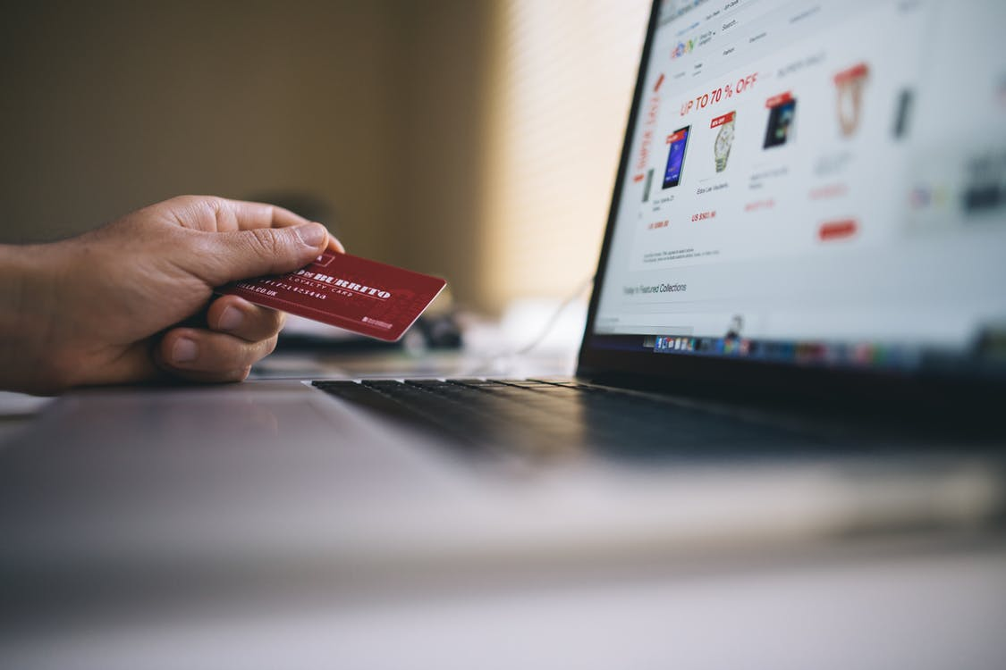יד שמחזיקה כרטיס אשראי מול מחשב עם אתר קניות פחות בדפדפן