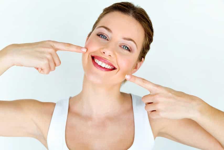 בחורה צעירה מחייכת ומצביעה על החיוך שלה