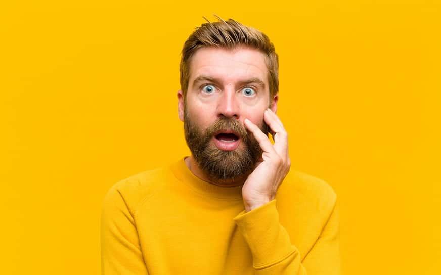 בחור בלונדיני עושה מבט מאוד מופתע על רקע צהוב